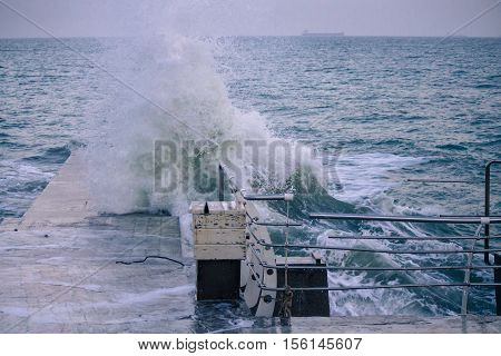 pier with Powerful sea splash wave with sprays and foam with vessel on the background. railings are broken because of huge wave.