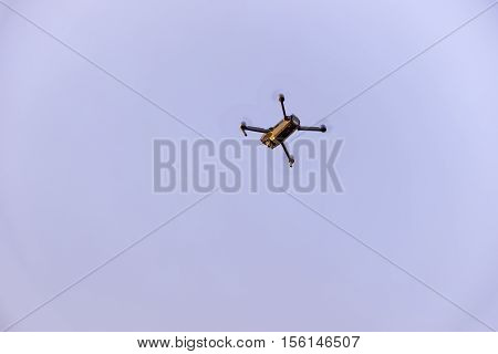 Close up of small modern drone taking photo while hovering against blue sky