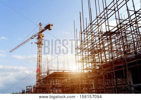 Modern building site workers and scaffolding and cranes.