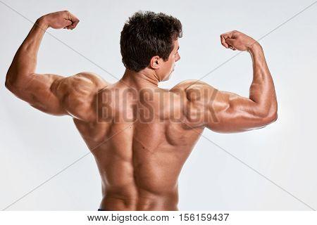 Athlete muscular bodybuilder showing back in studio on light grey background