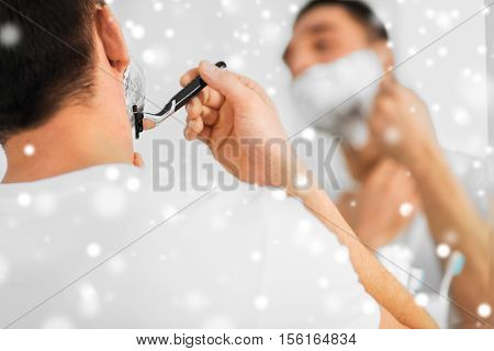 beauty, shaving, grooming and people concept - close up of young man looking to mirror and shaving beard with manual razor blade at home bathroom over snow