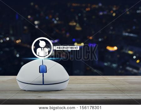 Wireless computer mouse with businessman and magnifying glass icon on wooden table over blur light city tower Recruitment concept
