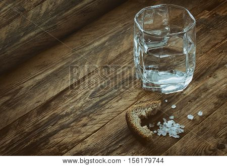 glass of water crust of black bread salt on old wooden table concept of hunger need