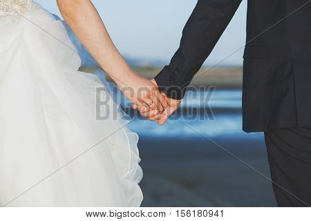 Wedding. Couple holding hands on the beach.