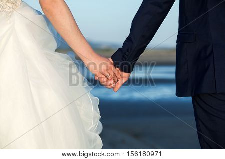 Wedding .Couple holding hands on the beach.