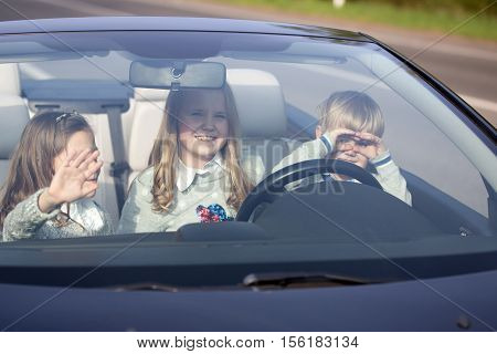 Cute three baby children friends of girls and boy people with at wheel pretends driving car as drivers on road outdoor