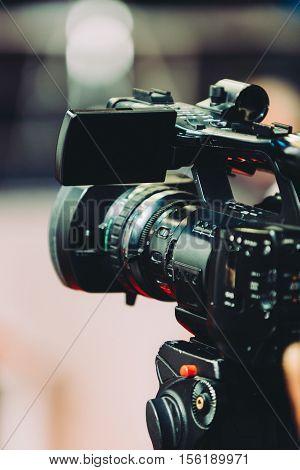 TV camera recording press conference, toned image