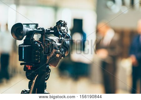 Television camera recording event, toned image, horizontal