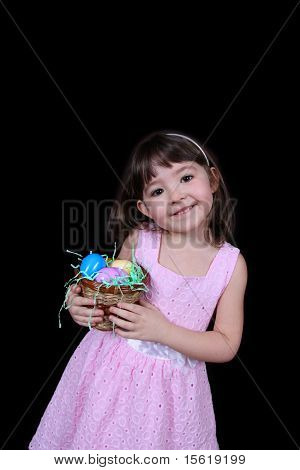 cute little girl holding a basket of colorful easter eggs isolated on black