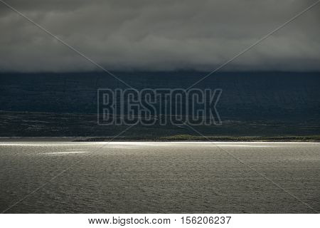 Dramatic landscape sunlight on lake and clouds covering the mountain