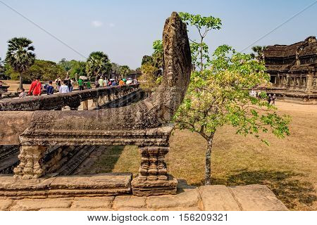 Siem Reap, Cambodia - February 1, 2016: Unidentified tourists visit to Angkor Wat temple Siem Reap Cambodia. Naga serpent cobra king Vasuki in the foreground guards the main road to the Angkor Wat
