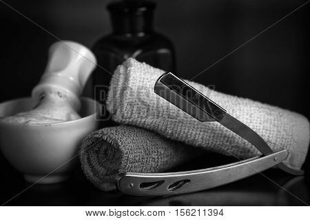Men's cosmetics shaving brush and straight razor in a wooden basket