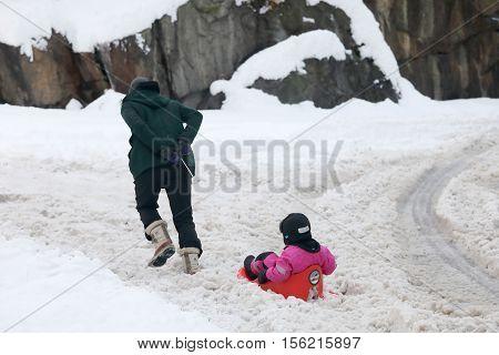 STOCKHOLM SWEDEN - NOV 10 2016: Father pulling a sledge with his child on the way to the kindergarten. November 10 2016 in Stockholm Sweden