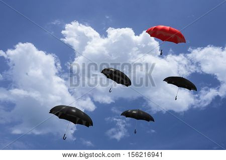 3D Rendering : Illustartion Of Red Umbrella Floating Above On Many Black Umbrellas Against Blue Sky