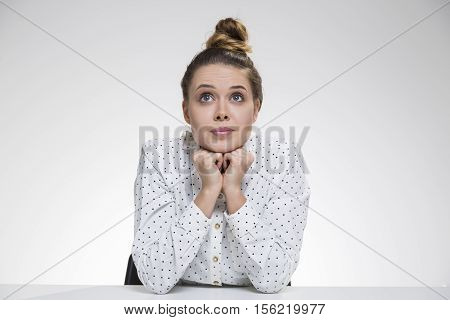 Dreamy girl in polka shirt is daydreaming with eyes wide open and her chin on her hands. Concept of dreaming. Mock up