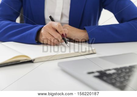 Woman's hands taking notes. She is wearing blue blazer and sitting at the table with laptop. Mockup