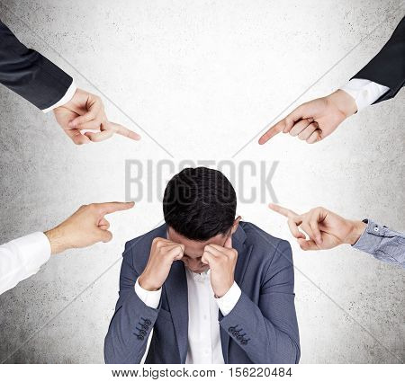 Four hands pointing at Asian businessman who is stressed out. Concept of blaming and shaming