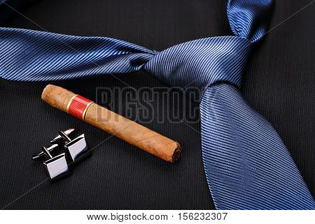 fancy blue tie with cufflinks and cigar
