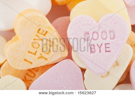 Many candy hearts with text as love you and goodbye