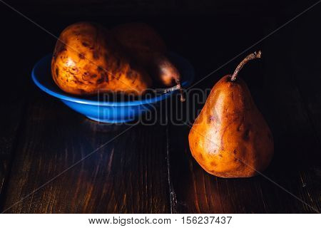 Golden Pears in Blue Bowl and One Pear Near.