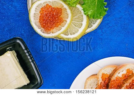 Salted salmon roe on the toasts and lemon slices over spotty blue background. Closeup. Flat lay