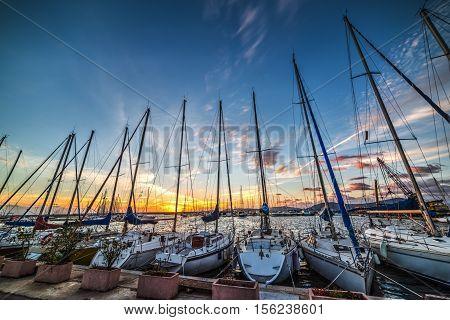 boats masts in Alghero harbor at sunset Italy