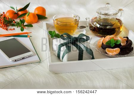 Green mint tea mandarin slices chocolate and gift box on tray near notebook pens mobile mandarins mountain ash sprig on white artificial fur background. Happy time break and gift. Close.