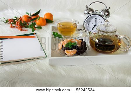 Green mint tea chocolate mandarin slices and alarm clock on tray near notebook pencils mandarins mountain ash on white artificial fur background. Morning time breakfast notebook plan preparation.