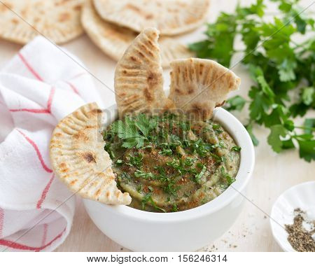 Eggplant dip in a white ceramic bowl with parsley and whole grain flat bread on a light wooden background