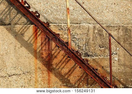 Iron rusty abandoned staircase on the background of a concrete wall. Urban landscape, abstraction. Laconic forms. The ladder casts a shadow on the wall. On the wall of the flow of rust. The staircase is visible from the side, down from the bottom