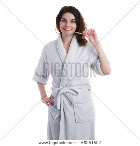 Smiling young woman in bath robe over white isolated background with toothbrush, morning, healthy, relaxation and beauty concept