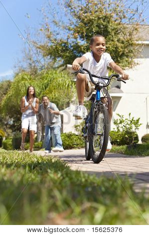 African American Family With Boy Riding Bike & Happy Parents