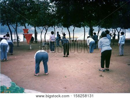 WUZHOU / CHINA: CIRCA 1987: Senior citizens exercise during the early morning in a park near the Li River.