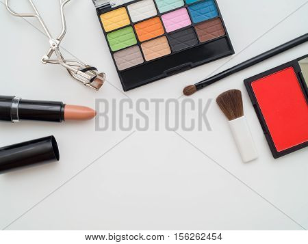 Top view of make up cosmetic products - eyeshadow lipstick eyelash curler brush on brush - on white background