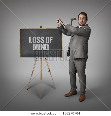 Loss of mind text on blackboard with businessman drilling his head