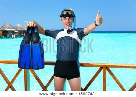 Young sports man with flippers mask and tube at ocean.Maldives