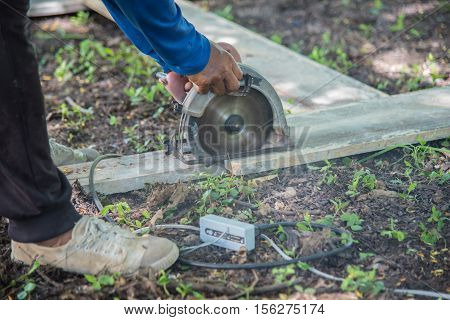Carpenter sawing wood board,carpenter chips from a circular saw at construction site