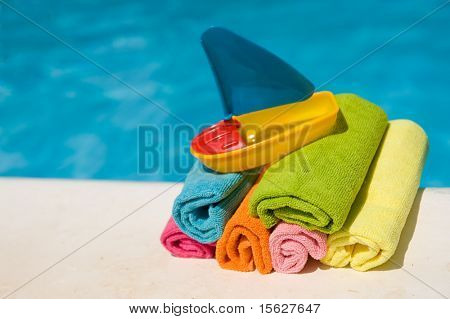 Gerollte Handtücher und Plastik Boot neben dem Schwimmbad