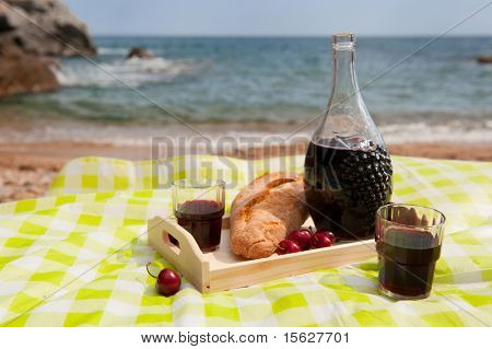 Wine bread and fruit at the picnic on the beach