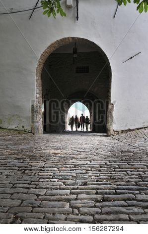 People Passing Through Old City Gate In Motovun, Croatia