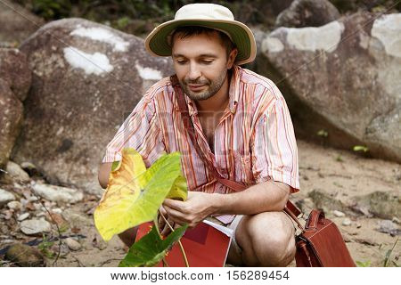 Handsome Bearded Biologist Wearing Hat Holding Leaf Of Green Plant, Looking With Friendly And Caring