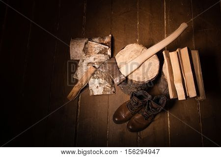 Style woodcutter. Lumberjack. Old woodcutter shoes. Brown shoes with laces. Lumberjack Accessories. Stump firewood an ax on a wooden background