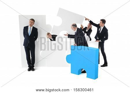 Lazy businessman and business team working concept people assembling puzzle isolated on white