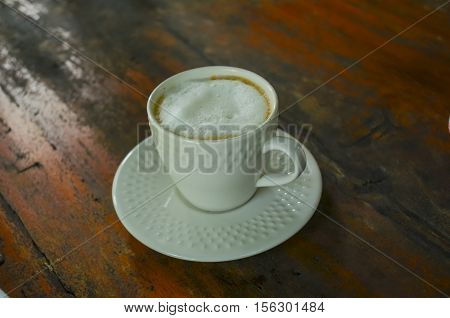 Coffee cup on a wooden table. Dark background