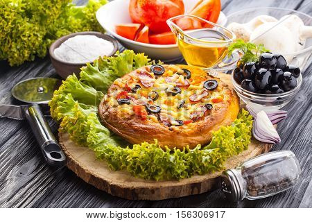 Delicious Homemade pizza and ingredients served on the black wooden table