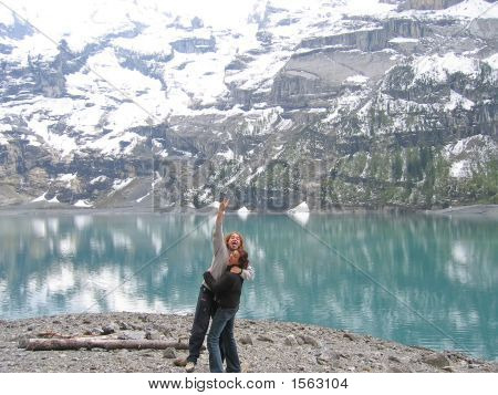 A Woman And A Jumping Man On A Mountain Lakeshore, Oeschinensee Lake, Switzerland