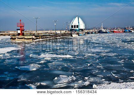 Winter sunrise in frosen harbor, Poland, Baltic Sea