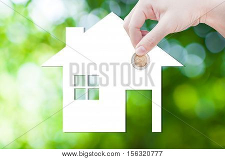 Coin Hand holding house icon in nature as symbol of mortgageDream house on nature background isolated on white background