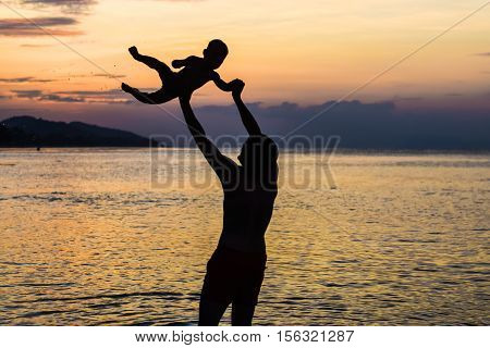 Young Happy Father Holding Up In His Arms Little Son Putting Him Up At The Beach In Barefoot Standin