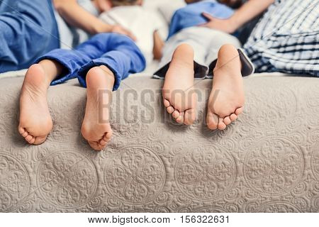 Time with family is time well spent. Close up of feet of sleeping children in bed room and lying near their parents
